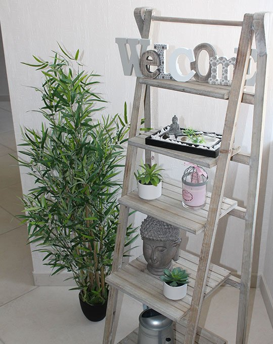 Photographie d'une étagère en bois avec des petites décorations zen, et un grand bambou apposé à côté.